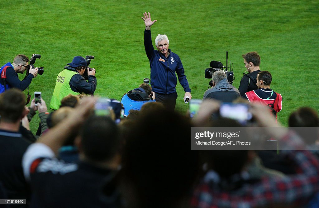Blues head coach Michael Malthouse walks off the ground through a Guard Of Honor formed by players after his record 715th game as a coach during the round five AFL match between the Carlton Blues and the Collingwood Magpies at Melbourne Cricket Ground on May 1, 2015 in Melbourne, Australia.