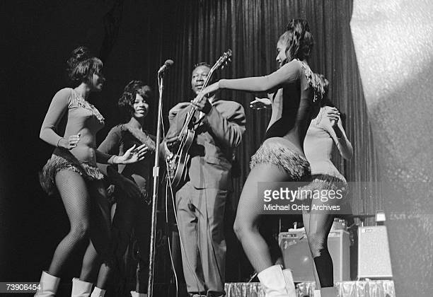 Blues musician BB King performs onstage with his Gibson hollowbody electric guitar nicknamed Lucille and back up dancers in 1963 at the Apollo...