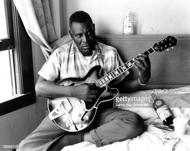 Blues musician Howlin' Wolf poses for a portrait in a hotel room holding a hollowbody electric guitar and sitting on a bed with a bottle of Ancient...