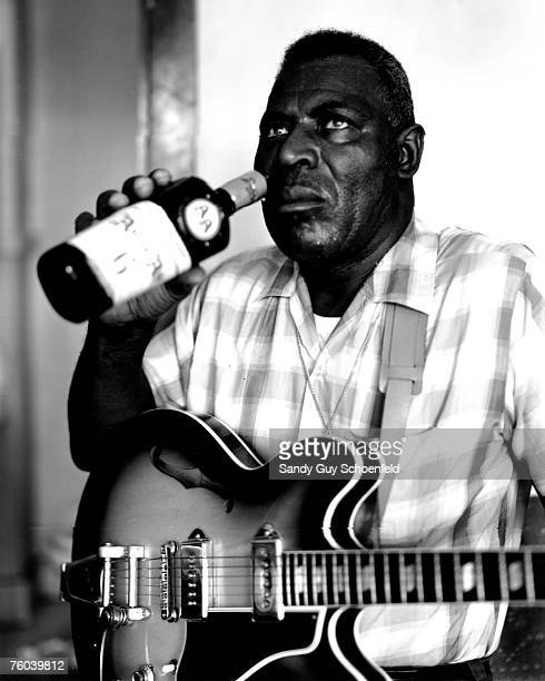 Blues musician Howlin' Wolf poses for a portrait in a hotel room holding a hollowbody electric guitar and sipping a bottle of Ancient Age whiskey in...