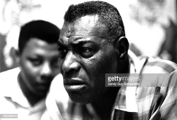 Blues musician Howlin' Wolf poses for a portrait in the hotel room after his show at the Fillmore with guitarist Hubert Sumlin in the background in...