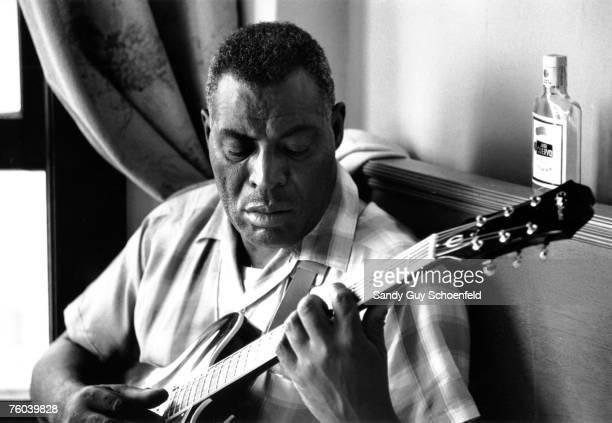 Blues musician Howlin' Wolf poses for a portrait with an Epiphone hollowbody electric guitar in front of a bottle of Jose Cuervo tequila in a hotel...