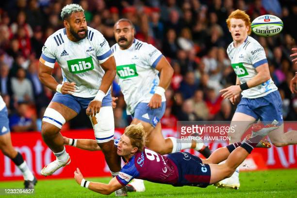 Blues' Patrick Tuipulotu is tackled by Reds' Tate McDermott during the Super Rugby Trans-Tasman match between the Queensland Reds and Auckland Blues...