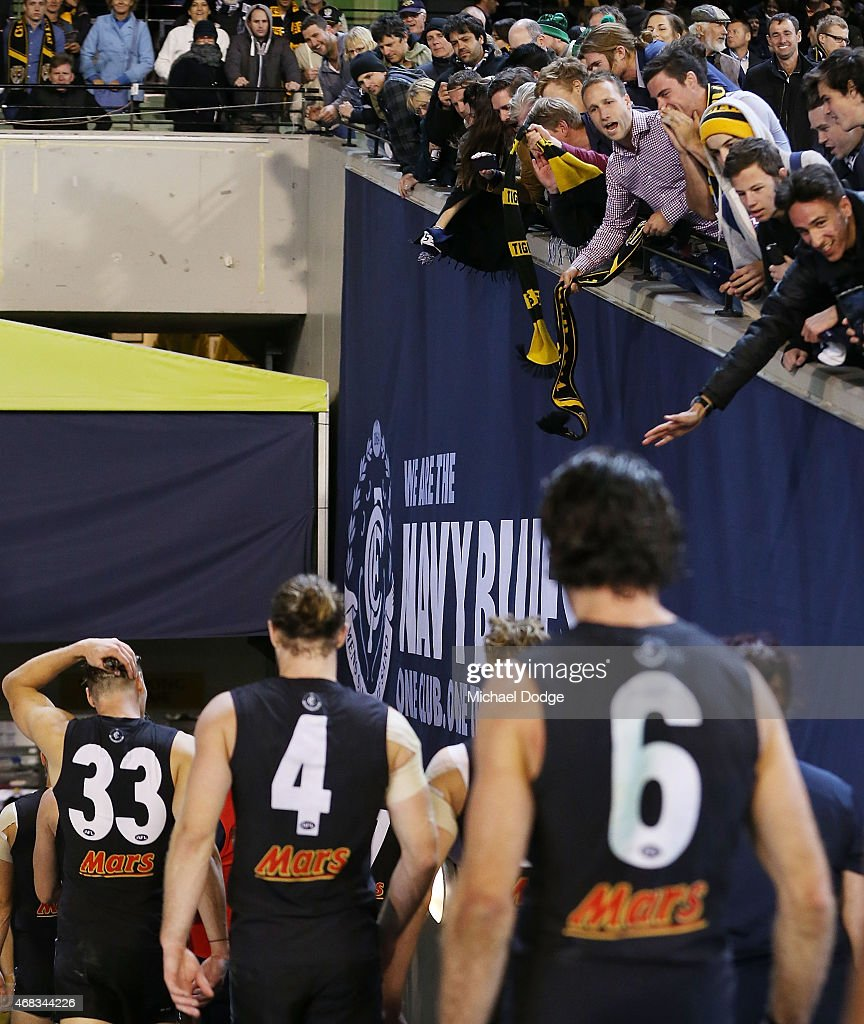 Blues players walk off after defeat as victorious Tigers fans dangle scarves in front of the during the round one AFL match between the Carlton Blues and the Richmond Tigers at Melbourne Cricket Ground on April 2, 2015 in Melbourne, Australia.