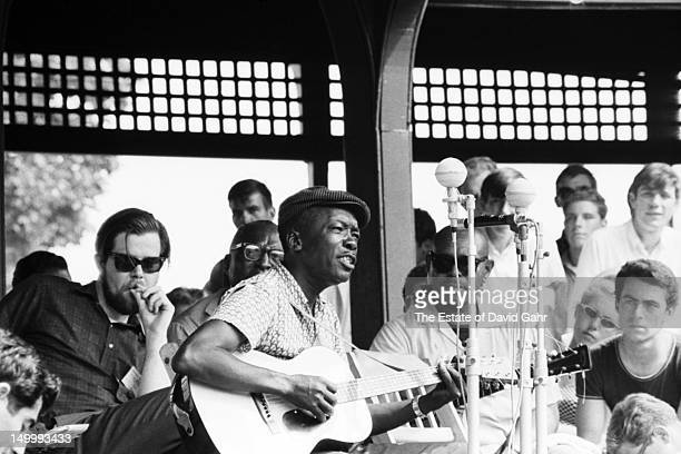 Blues singer and musician John Lee Hooker performs at the Newport Folk Festival in July 1963 in Newport Rhode Island Sharing the stage are Dave Van...