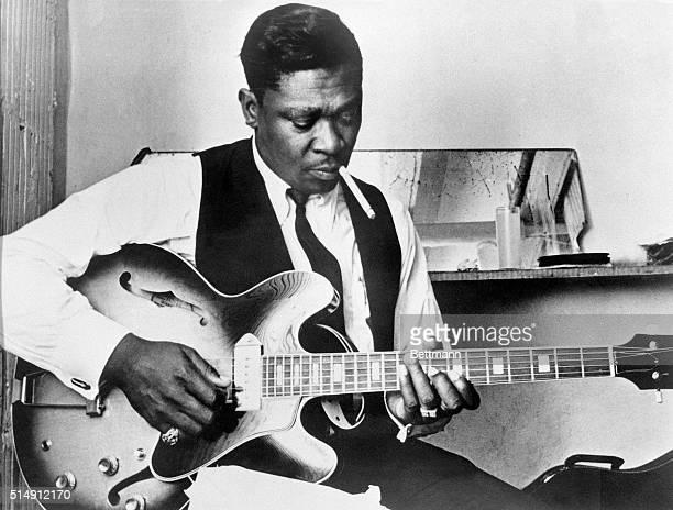 Blues singer BB King playing guitar and smoking