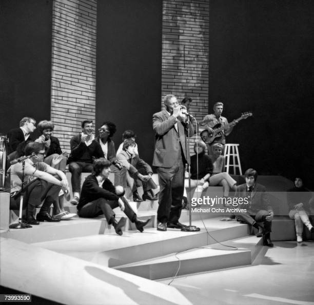 """Blues singer Howlin' Wolf performs on the TV Show """"Shindig"""" as the rock and roll band """"The Rolling Stones"""" and Darlene Love look on."""