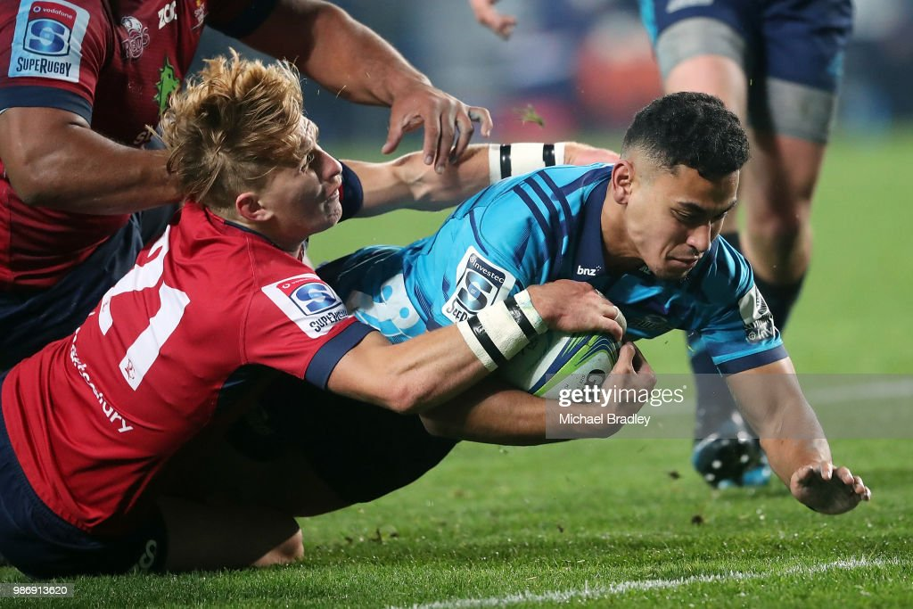 Blues Stephen Perofeta (R) dives over for a try in the tackle of Reds Tate McDermott during the round 17 Super Rugby match between the Blues and the Reds at Eden Park on June 29, 2018 in Auckland, New Zealand.
