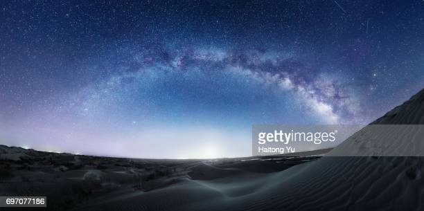Blue-tone image of milky way over sand dunes