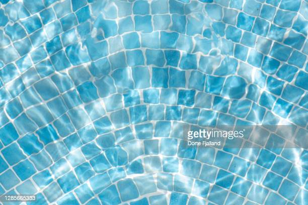 bluish mosiac in a swimming pool with water moving - dorte fjalland ストックフォトと画像