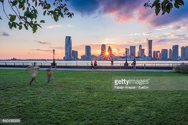 Blur Image Of Father And Daughter Running On Grassy Field By Sea And Modern Buildings During Sunset