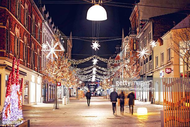 blur image of people walking on street amidst illuminated buildings decorated with christmas lights - stadsstraat stockfoto's en -beelden