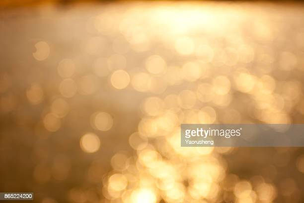 Blur sunset beach with bokeh sun light wave abstract background