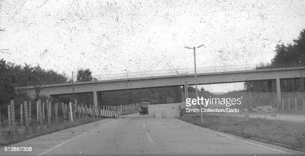 Blurred and damaged photo of military vehicles cars and a highway overpass at a checkpoint on the border between East Berlin and West Berlin during...