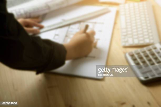blurred background Close-up hand Of male Architect Drawing Blueprint on work space wooden table in office