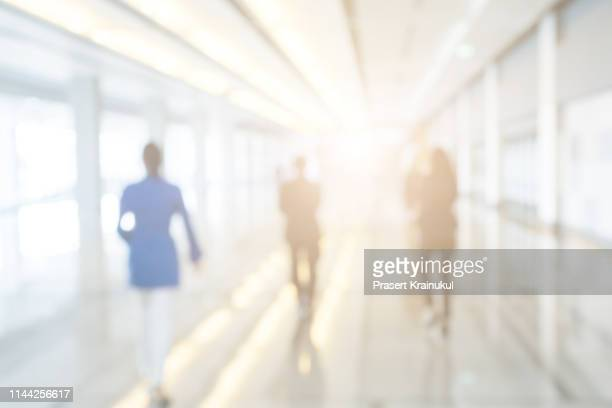 blurred background of businesspeople standing in the corridor of an business center - office background stock pictures, royalty-free photos & images