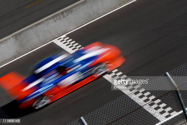 Blurred Blue Orange Race Car Crossing Checkered Finish Line