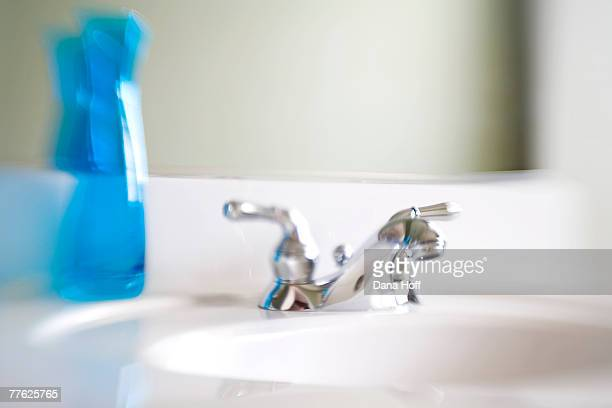 blurred blue vase and silver faucet on white bathroom counter - dana white stock pictures, royalty-free photos & images