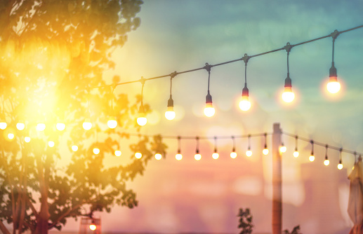 blurred bokeh light on sunset with yellow string lights decor in beach restaurant 1144248362