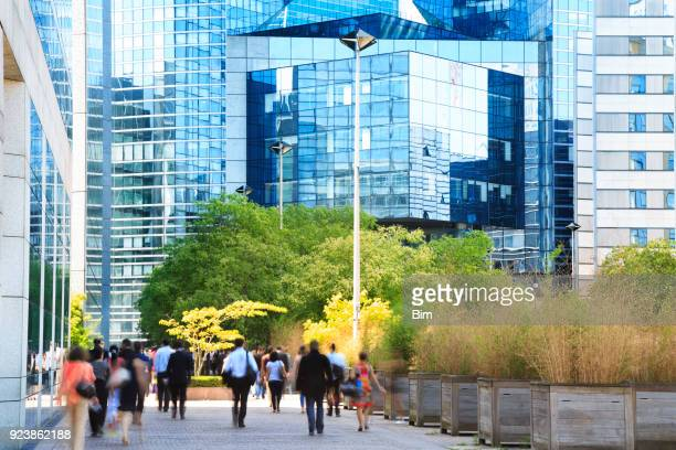blurred business commuters walking in financial district, la defense, paris, france - business community stock pictures, royalty-free photos & images