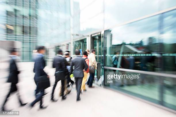 blurred business people entering office building through glass doors - entering stock pictures, royalty-free photos & images