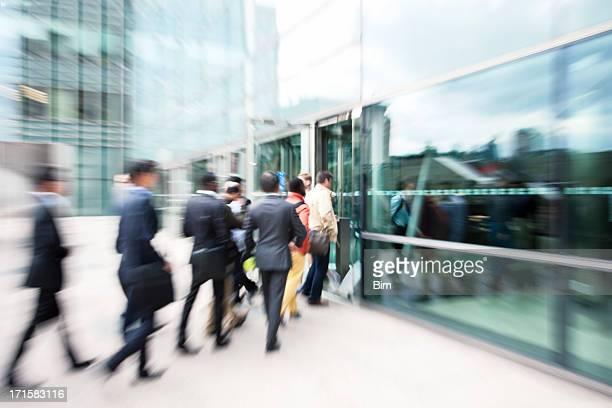 Verschwommene Geschäftsleute, die im Büro-Gebäude durch Glastüren