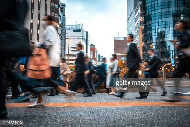blurred business people on their way from work - colletti bianchi foto e immagini stock