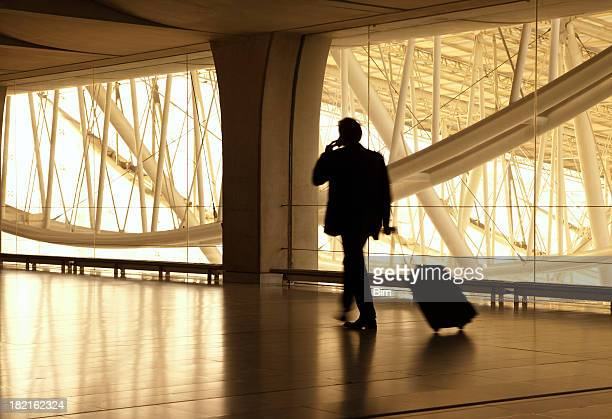 Blurred Businessman at Airport, Pulling Suitcase, Using Mobile Phone