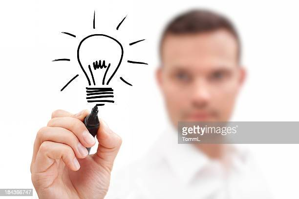 Blurred businessman drawing a lightbulb showing an idea