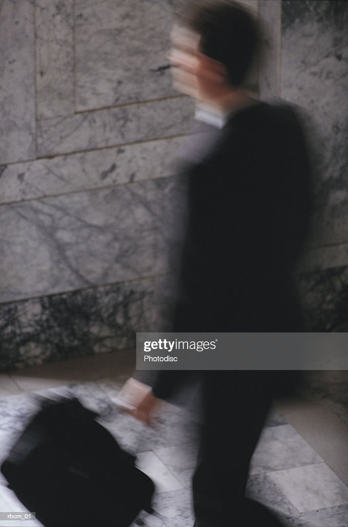 A blurred businessman in a black suit carries a brief case as he walks : ストックフォト