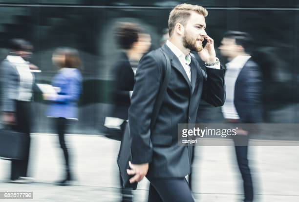 Blurred Businessman Walking Outdoors Talking on the Phone