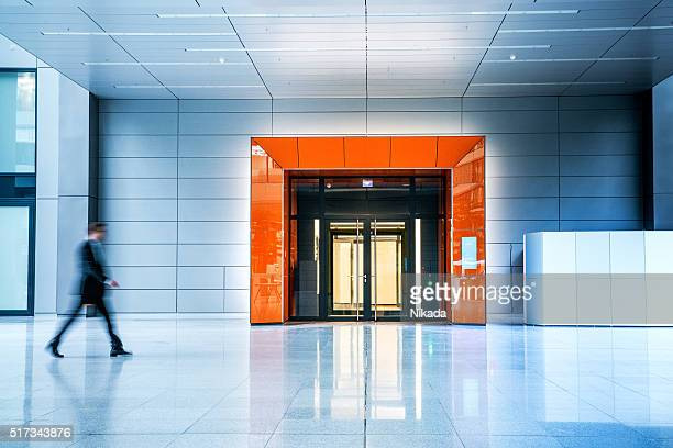 blurred businessmen walking inside a modern building - hotel lobby stock pictures, royalty-free photos & images