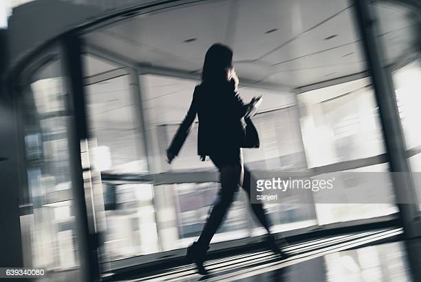 Blurred Businesswoman Walking Through Office Entrance Using Smart Phone