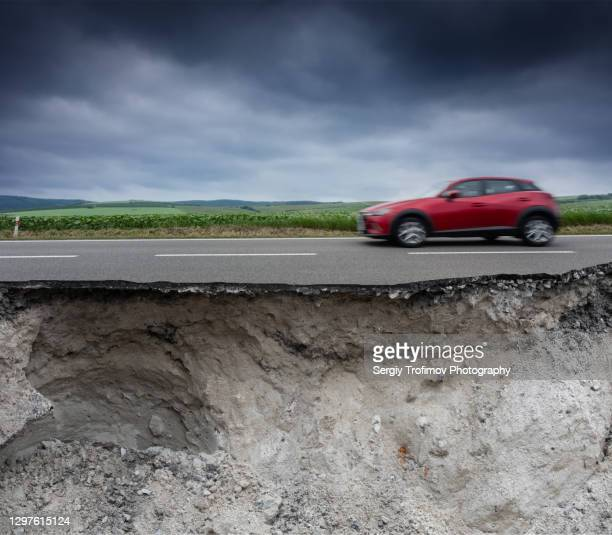 blurred car is driving on broken road with cracked asphalt - empty road stock pictures, royalty-free photos & images