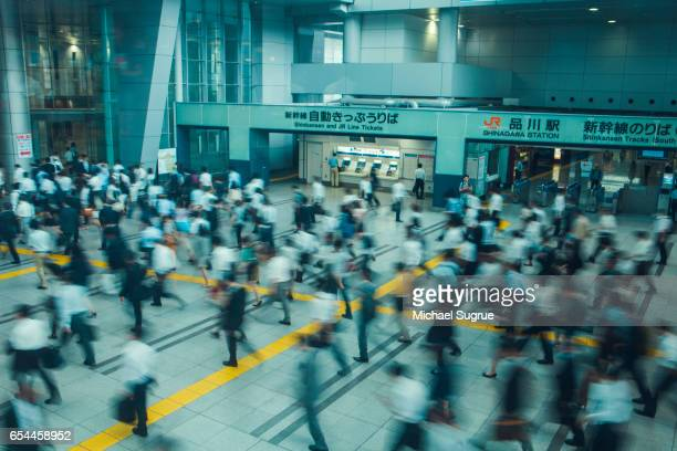 Blurred commuters rush to work at Shinagawa Station in Tokyo, Japan.