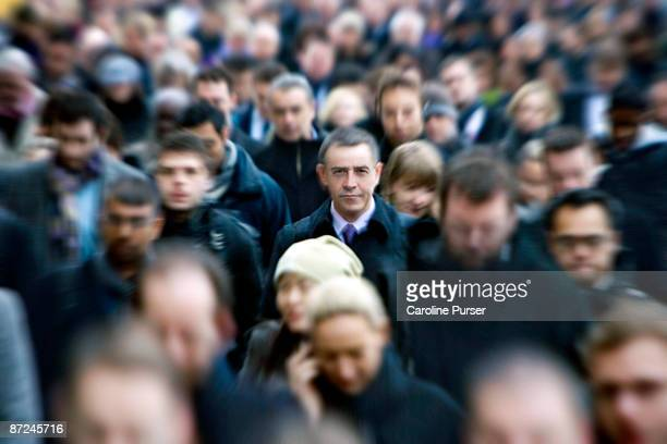 blurred commuters with one man in focus - menschenmenge stock-fotos und bilder