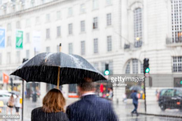 blurred couple walking in rain at regent street lodon - torrential rain stock pictures, royalty-free photos & images