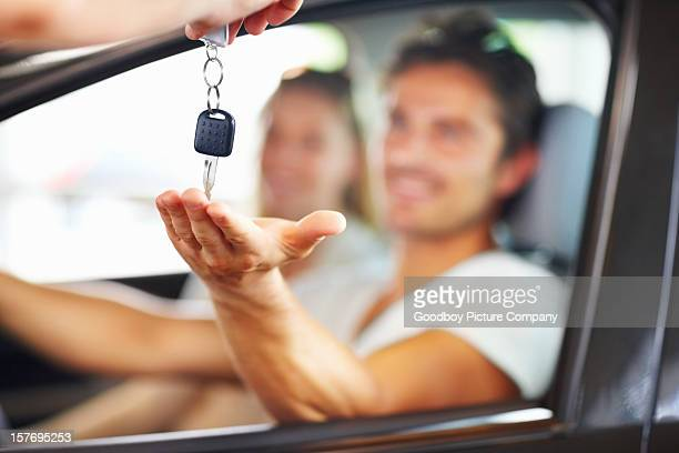 Blurred couple with man receiving car key from salesman