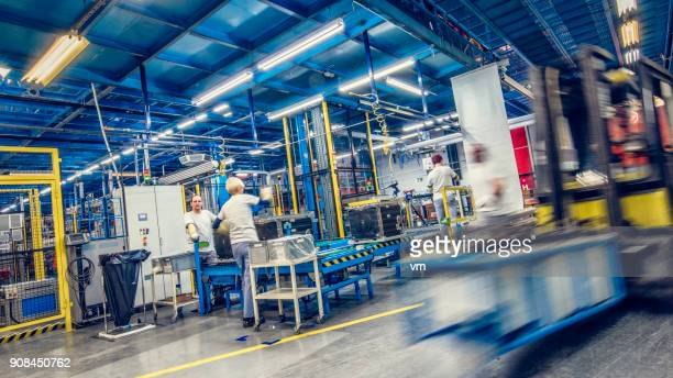 Blurred forklift and factory workers