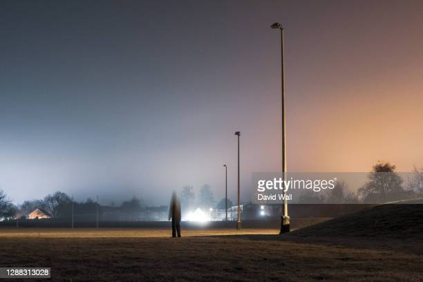 a blurred, ghostly figure standing on sports field with flood lights on a moody foggy winters night - town stock pictures, royalty-free photos & images