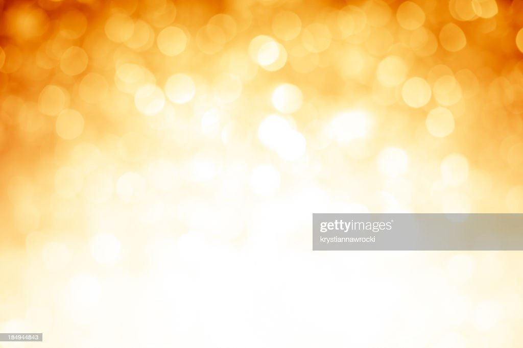 Blurred gold sparkles background with darker top corners : Stock Photo