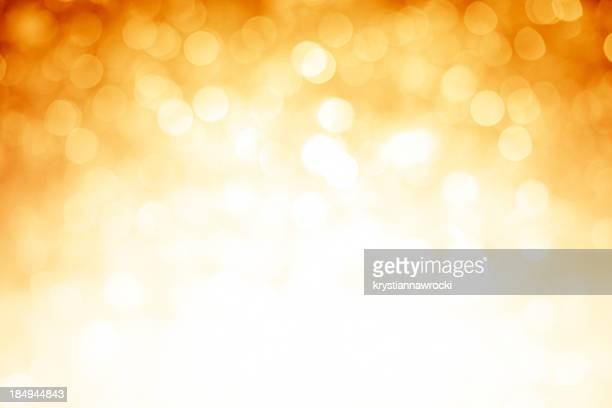 Blurred gold sparkles background with darker top corners