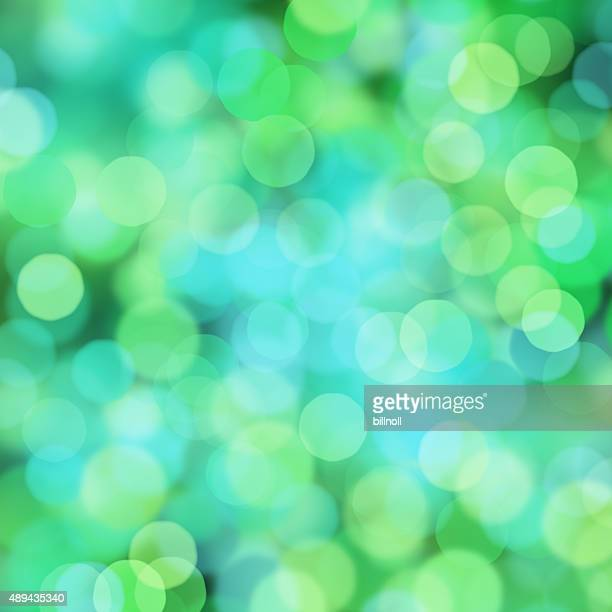 Blurred green and blue bokeh dots on black background