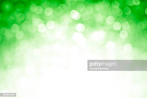 Blurred green sparkles background with darker top corners, bright center