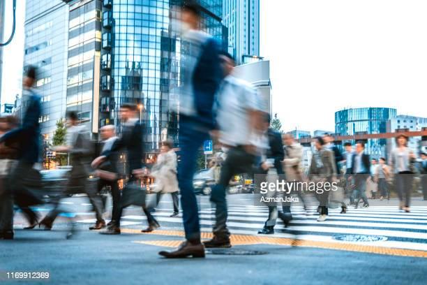 日本の路上で通勤するビジネスマンのぼやけたグループ - 混雑した ストックフォトと画像