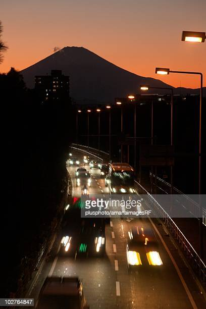 blurred headlights on highway in front of mt. fuji. kanagawa prefecture, japan - plusphoto stock pictures, royalty-free photos & images