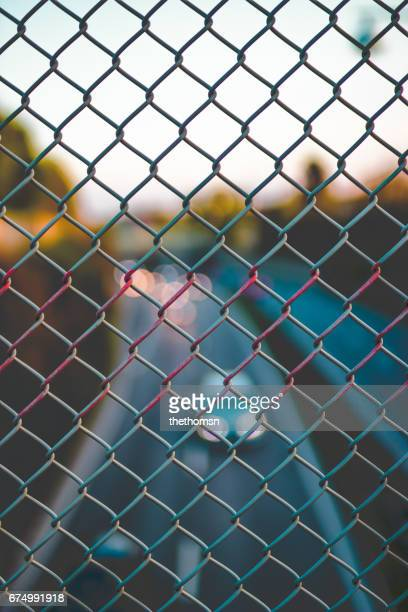 blurred highway traffic thru a fence at sundown, germany - städtische straße stock pictures, royalty-free photos & images