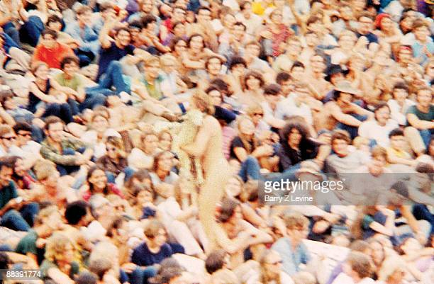 Blurred image of an apparently naked man as he carries a sheep through a crowd of bemused onlookers in attendance at the Woodstock Music and Arts...