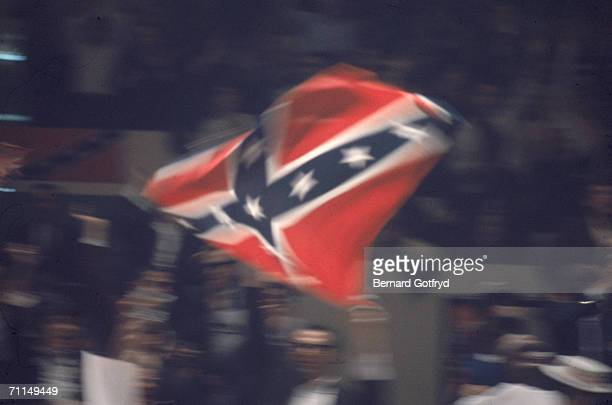 A blurred image of an attendee waving a Confederate States of America battle flag at the national convention of the American Independent Party at...