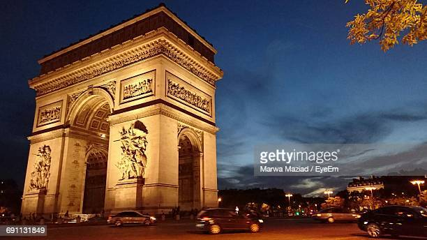 Blurred Image Of Cars On Street By Arc De Triomphe Against Sky At Night